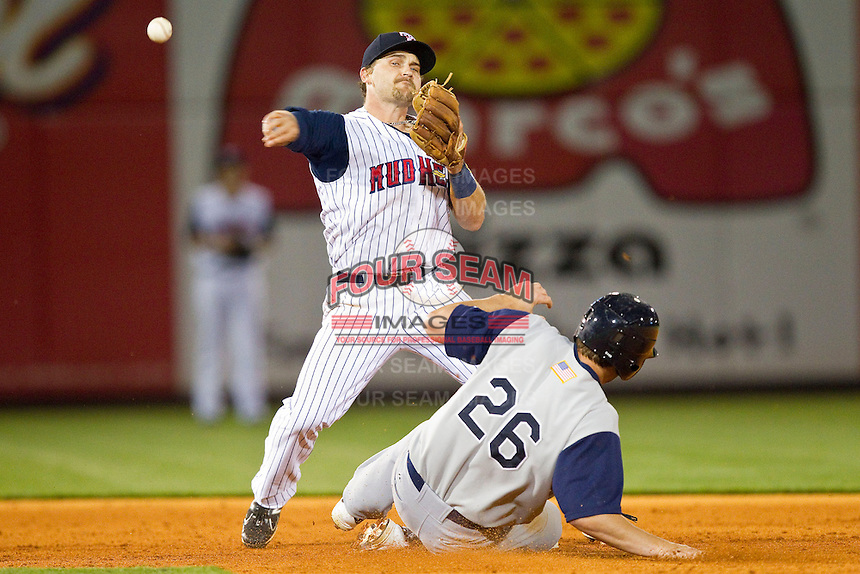 Brandon Douglas (4) of the Toledo Mudhens attempts to turn a double play as Brent Morel (26) of the Charlotte Knights slides into second base at 5/3 Field on May 3, 2013 in Toledo, Ohio.  The Knights defeated the Mudhens 10-2.  (Brian Westerholt/Four Seam Images)
