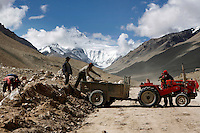 "Workers with their bare hands load rocks on a truck to build the road to Mt Everest.China started building a controversial 67-mile ""paved highway fenced with undulating guardrails"" to Mount Qomolangma, known in the west as Mount Everest, to help facilitate next year's Olympic Games torch relay."