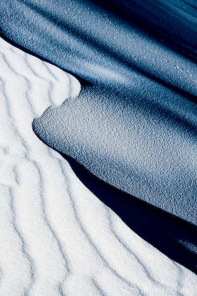 Monochrome abstract image tracing the curve in a white sand dune