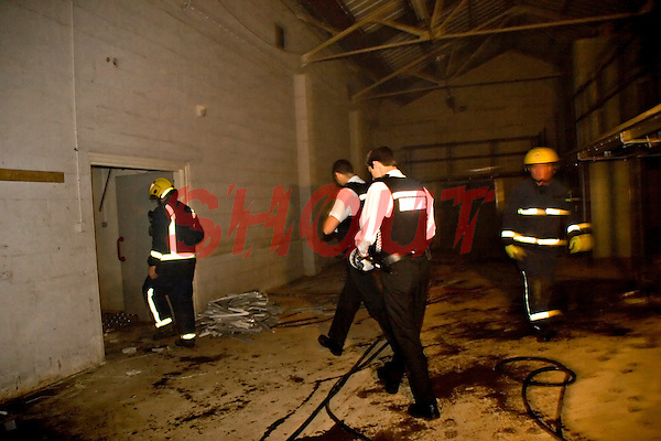 Police officers and Firefighters inside a factory unit which has been set alight by arsonists. This image may only be used to portray the subject in a positive manner..©shoutpictures.com..john@shoutpictures.com