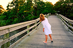 On long wood pier, girl looks back at Woods, at Norman J Levy Park and Preserve on Long Island, New York, USA in summer.