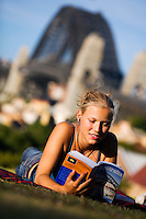 A backpacker reads her guidebook in Observatory Park, overlooking Sydney harbour.  Sydney, New South Wales, AUSTRALIA