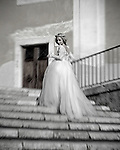 A woman pauses in her wedding dress at the top of an outdoor stairway in Rome, Italy, looking back over her shoulder with smile.
