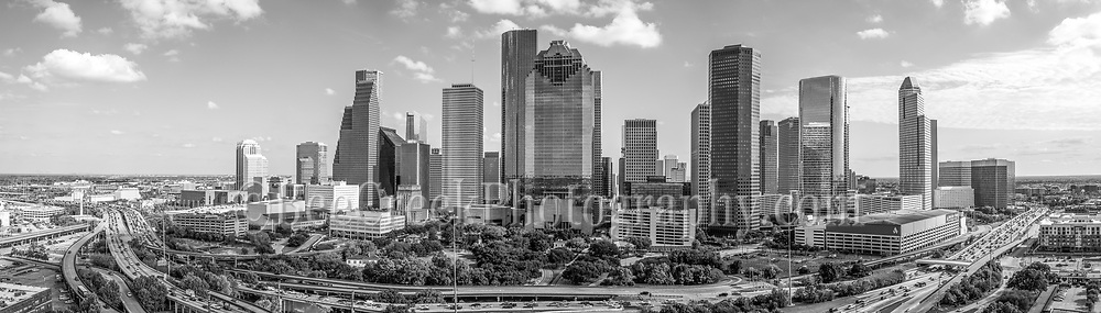 Capture this black and white aerial panorama of Houston Skyline during the day in downtown. We wanted to capture downtown Houston skyline with IH45 in view so an aerial was our best option so this area of the cityscape is looking at the Theater district of the city. Houston also has a reputation of a place to see top notched performing art along with access to several museums in the area. The Theater distric performing art has nine major performing art group along with six performance halls. You can see Opera, a plays, the ballet and any number of music events including the well known Houston Symphony Orchestra. Houston is a large city with a population around 2.3 million people which makes it the fourth most populous city in the US and the biggest in Texas and the southern US. The skyline of Houston is a very impressive site with some of the tallest modern skyscrapers buildings in the US. In this image you can see the Heritage Plaza, Chevron, Wells Fargo and the tallest building in Houston the J P Morgan Chase Tower at 1002 ft and it is the 17 tallest in the US. Houston is the seat of Harris county and was founded in 1837 near the banks of the Buffalo Bayou or Allen Landing as it is called today. The city was name after General San Houston after he won the battle of San Jacinto. Houston has been a growing city because of the port of houston and railroads along with oil boom from the early 1901. Houston has other industry that have made it thrive in america such as energy, manufacturing, aeronautics, and transportation. Also NASA mission control is located in the city. Houston has also taken the lead on health care with many people coming to the Medical Center for top notch doctors and hospital with the latest advancement in medical