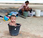 Jesus Miguel Moraleda, a one-year old Warao indigenous boy from Venezuela, bathes in a bucket as his mother does laundry behind him in Boa Vista, Brazil. The boy and his family live in a park in Boa Vista that they and other Warao refugee families invaded. They had previously been sheltered in a government refuge, but found the military-controlled environment oppressive. So they moved out and set up their own refuge in the park, where they receive some support from local Catholics.