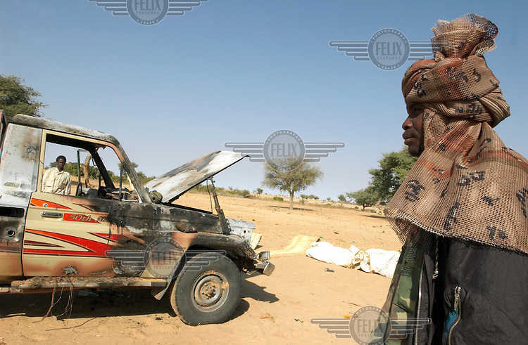 Chadian soldiers inspect one of their jeeps that they claim was bombed by a Sudanese plane in the Chadian village of Besa in late December 2003. The soldiers say they were attacked while approaching a Sudanese helicopter that crash landed in Chadian territory.
