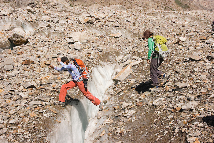 Two women ski mountaineers jumping a crevasse on the Biafo glacier in the Karakoram mountains of Pakistan