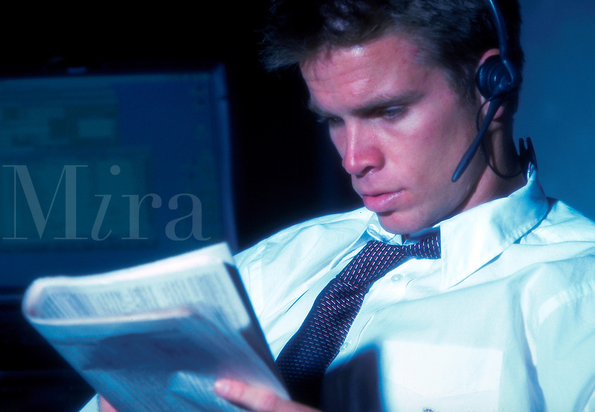 A young executive man talking into a phone headset withnlooking at a newspaper with a serious expression.