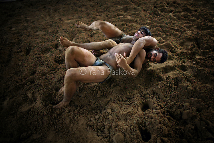 Indian men practice traditional Kushti wrestling on Monday, June 01, 2009 in New Delhi, India. ..---------------------..Story Synopsis:  Kushti, India's indigenous form of wrestling, has gone from a royal national sport to a dying art in Asia over the past century.  Those who still practice it meet the lengthy hours of its daily regimen with unrelenting devotion -- rope, aerobic and weight exercises; culturing the soil on which they wrestle; a diet comprised of non-spicy, self-made food; and celibacy.  And so, in traditional earthen pits wrestlers still apply the physical and mental intensity that has driven their ancestors for three thousand years.  But a 2004 decision by the Indian Fighters Federation from the capital of Delhi, prohibiting fighting on red soil and ordering fight clubs to use mattresses instead, exacerbated Kushti's diminishing role in Indian tradition.  The order was in part an effort to gather more Olympic medals -- the first by Khashaba Dadasaheb Jadhav, a bronze in 1952, and most recently, also a bronze at the 2008 Beijing Olympics, by Sushil Kumar.