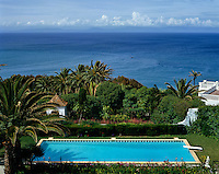 View of the Mediterranean from a property with a secluded swimming pool nestling among tropical trees