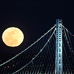The February full moon rose over the new Bay Bridge tower as seen from Pier 39 in San Francisco, CA.
