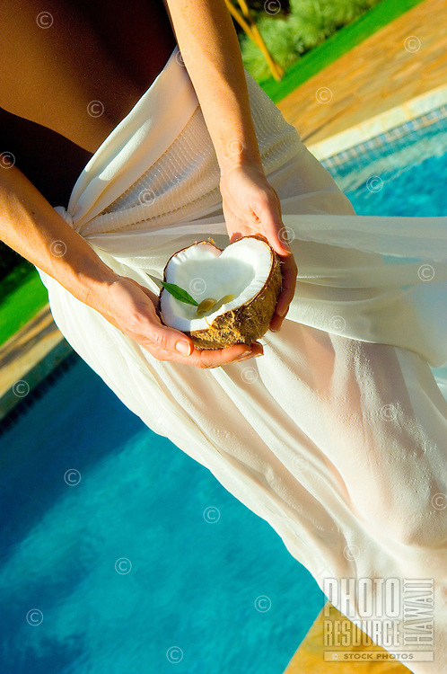 Woman In Sarong, Hands Holding Split Coconut Poolside