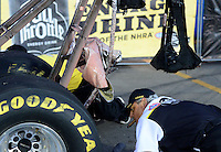 Nov. 11, 2012; Pomona, CA, USA: NHRA Safety Safari member looks at the oil soaked wing struts and parachute packs of the top alcohol dragster during the Auto Club Finals at at Auto Club Raceway at Pomona. Mandatory Credit: Mark J. Rebilas-