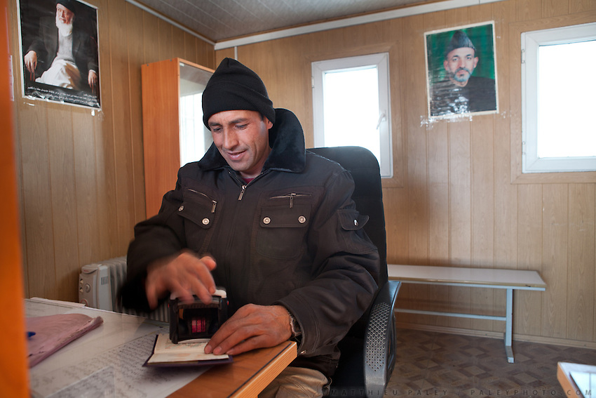 A custom officer stamps a passport, on the entry point into Afghanistan, from Tajikistan, at the town of Ishkashim.