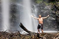 Local Hawaiian looking shirtless man standing with arms spread beneath Waimoku Falls waterfall on Maui in Hawaii