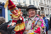 Covent Garden, London, UK. 11 May 2014. The festival starts with a procession around the streets of Covent Garden. A female puppeteer holds a Mr Punch puppet. The Covent Garden May Fayre and Puppet Festival takes place at St Paul's Church.