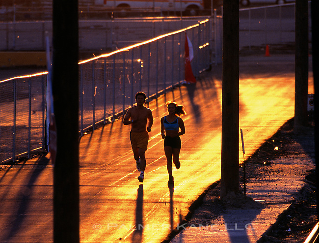 Young couple jogging along city streets as sunset approaches