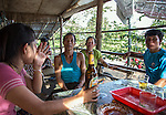 19 October 2013, Pakse, Laos:  Fisherman Kao Vonesaksith ( blue singlet , centre) from Kon Kaen village sitting in a bamboo cafe with family by the Mekong River where yesterday he found the bodies of two passengers from the ill fated  Lao Airlines plane that crashed upstream into the Sedon River 20 kilometres away in Pakse. The aircraft crashed into the Mekong River tributary on approach to Pakse airport from Vientiane in severe weather killing all 44 passengers and 5 crew on board including six Australians. Rescue workers are still dragging the fast flowing river for further remains and the main body of the plane.  Picture by Graham Crouch
