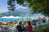 Austria, Upper Austria, Salzkammergut, Unterach am Attersee: hotel owned beach of Hotel and restaurant Stadler next to shipping pier Stockwinkel, at backgound Hoellen mountains with summit Brennerin (1602 m) | Oesterreich, Oberoesterreich, Salzkammergut, Unterach am Attersee: hoteleigener Badestrand des Hotel und Seegasthof Stadler am Schiffsanleger Stockwinkel, im Hintergrund das Hoellengebirge mit Brennerin (1602 m)