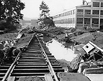 The Chase Metal Works in Waterville will not be reached by rail for some time, if the twisted wreckage of the tracks on the plant's spur are any indication. The low area between the factory and Route 8 was piled high with debris hurled into the area by the raging Naugatuck River. 22 August 1955.