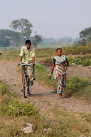 A man cycles past a women on a small dirt track on the outskirts of Kolkata<br />