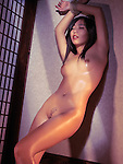 Beautiful naked Japanese woman standing at a wall with hands tied above her head and Ai - Love character tattoo on her body. Bondage Shibari artistic nude photo.