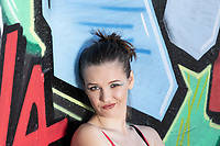 Head shot of Female leaning against a bright colored grafiti wall, making facial expressions
