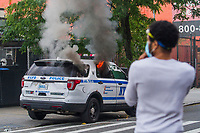 NEW YORK, NEW YORK - MAY 30: Protesters next to the car that was lit with fire during the protest in response to the police officer who killed George Floyd in Brooklyn on May 30, 2020 in New York. The protests spread across the country in at least 30 cities in the United States. United States For the death of unarmed black man George Floyd at the hands of a police officer, this is the latest death in a series of police deaths of black Americans (Photo by Pablo Monsalve / VIEWpress via Getty Images)