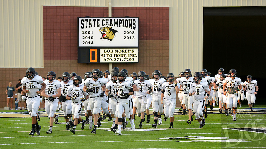 NWA Democrat-Gazette/BEN GOFF @NWABENGOFF<br /> The Bentonville offense takes the field on Saturday Aug. 22, 2015 before the varsity scrimmage during Tiger Pride night in Bentonville's Tiger Stadium.