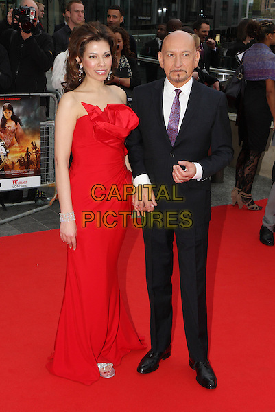 "DANIELA LAVENDER & SIR BEN KINGSLEY.The World Premiere of ""Prince Of Persia - Sands Of Time"", The Vue Westfield, London, England. .9th May 2010 .full length red strapless maxi dress silk satin black suit married husband wife holding hands .CAP/MAR.© Martin Harris/Capital Pictures."