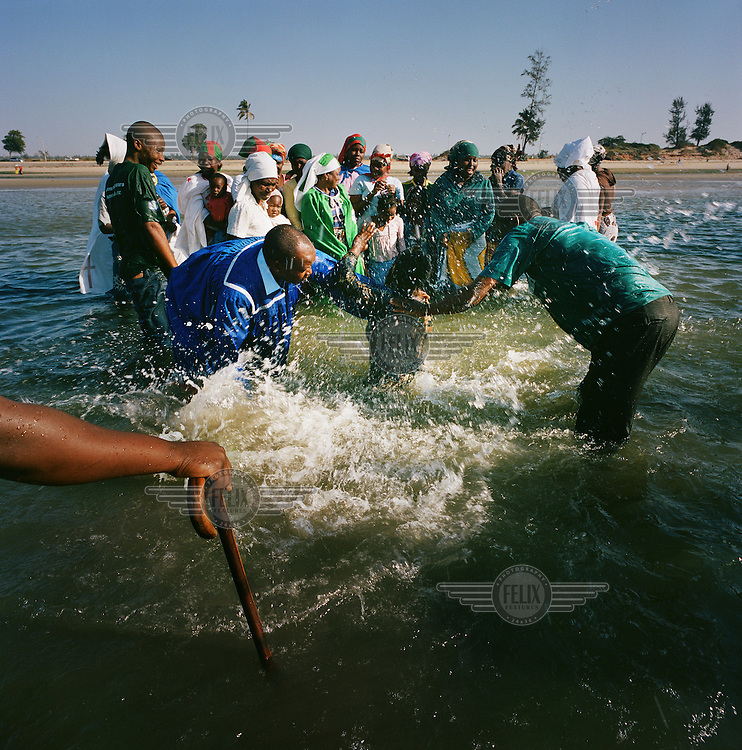 A woman in plunged into the sea during a purification ceremony held by adherents of a Zion church on a beach. Zion Churches in Mozambique are a rapidly expanding phenomenon that have evolved from extant social and cultural conditions. They feature the spiritual healing of misfortunes and illnesses and the use of protective drumming and dance against evil spirits and witchcraft.