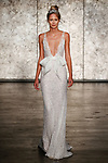 Model walks runway in a fully sequined crochet lace v neck sheath with organza pocketed waist bow, from Inbal Dror Fall 2018 bridal collection on October 5, 2017; during New York Bridal Fashion Week.