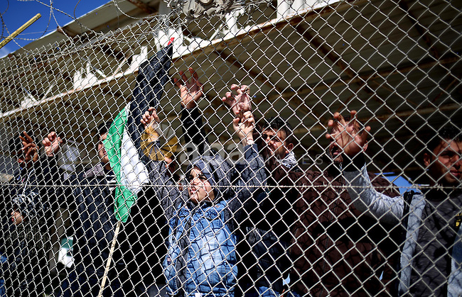 Palestinians stand behind a fence as they wait for the arrival of their relatives at Rafah crossing after it was opened by Egyptian authorities to allow stranded Palestinians to return to Gaza, in the southern Gaza Strip February 18, 2017. Photo by Ashraf Amra