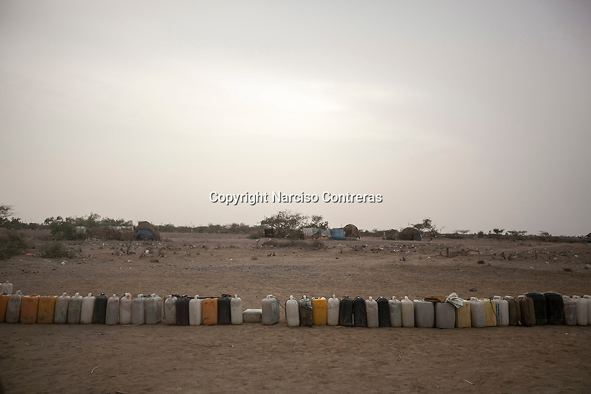 Tuesday 07 July, 2015: Containers are seen queueing as displaced (not pictured) from the heavy fighting in Haradh bordertown await for water distribution in a temporary settlement at the outskirts of Beni Hassan in Hajjah province, Northwest of Yemen. (Photo/Narciso Contreras)