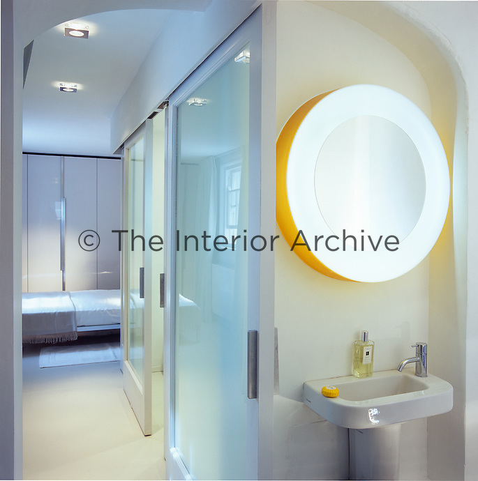 A round, lit mirror hangs above a pedestal washbasin in the corner of a bathroom. Beyond a pair of sliding glass doors is a bedroom with built-in wardrobes.