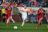 New York midfilder Dax McCarty (11) plays the ball in between Chicago midfielders Jeff Larentowicz (20, left) and Logan Pause (12, right).  The Chicago Fire defeated the New York Red Bulls 3-1 at Toyota Park in Bridgeview, IL on April 7, 2013.