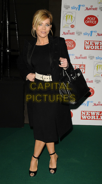 MICHELLE COLLINS.Children's Champions Awards 2009 at the Grosvenor House Hotel, Park Lane, London, England..March 4th 2009.full length black coat dress ankle strap peep toe shoes Christian Louboutin Hermes Birkin bag platform hand on hip white cream waist belt .CAP/CAN.©Can Nguyen/Capital Pictures.