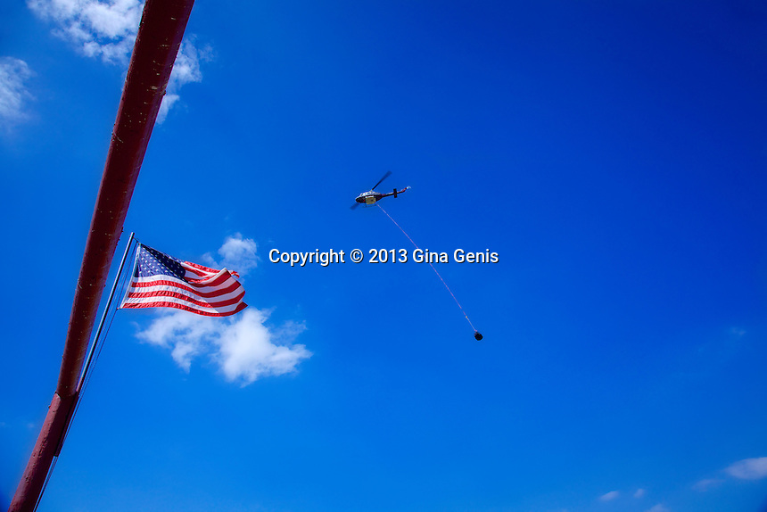 Helicopter flies above American flag as it long lines supplies to Hot Shots during the Mountain Center fire.