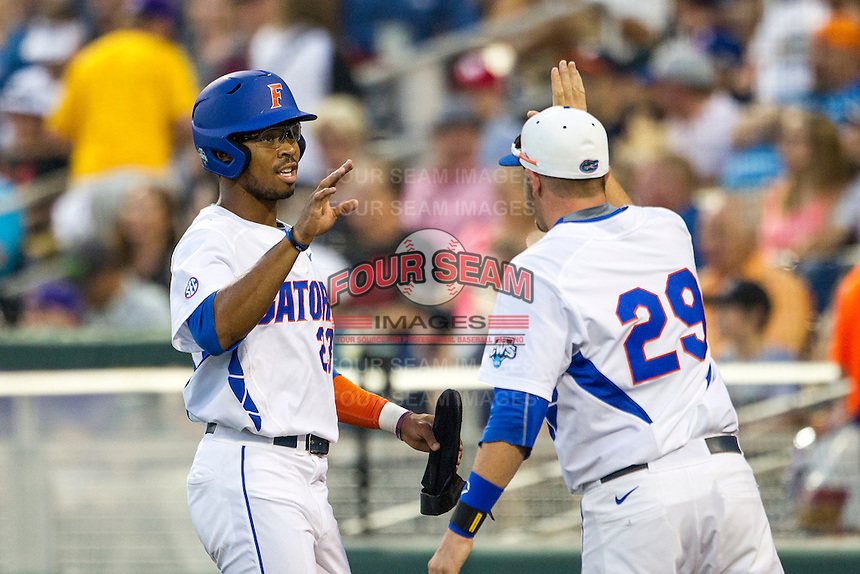 Florida Gators outfielder Buddy Reed (23) is greeted by teammate Mike Fahrman (29) after scoring against the Miami Hurricanes in the NCAA College World Series on June 13, 2015 at TD Ameritrade Park in Omaha, Nebraska. Florida defeated Miami 15-3. (Andrew Woolley/Four Seam Images)