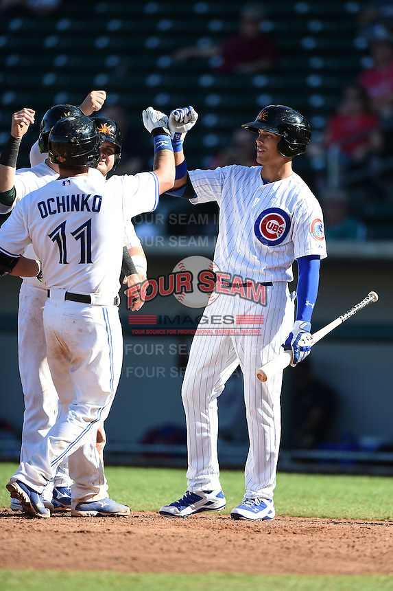 Mesa Solar Sox catcher Sean Ochinko (11) is greeted at home by Dan Vogelbach (back), Daniel Robertson (hidden) and Jacob Hannemann (17) after hitting a home run during an Arizona Fall League game against the Surprise Saguaros on October 17, 2014 at Cubs Park in Mesa, Arizona.  Mesa defeated Mesa 5-3.  (Mike Janes/Four Seam Images)