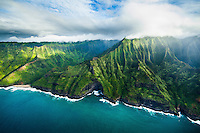 An aerial view of the steep cliffs, a beach and a deep cave of Na Pali Coast on Kaua'i.