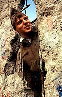 BERLINO / GERMANIA - 10 NOVEMBRE 1989.UN VOPOS SI AFFACCIA ATTRAVERSO UNA BRECCIA NEL MURO NELLA ZONA DEL CHECKPOINT CHARLIE..FOTO LIVIO SENIGALLIESI..BERLIN / GERMANY - 10 NOVEMBER 1989.ONE VOPOS, DDR BORDER SOLDIER, WATCHING TO THE WEST THROUGH THE WALL NEAR CHECKPOINT CHARLIE..PHOTO BY LIVIO SENIGALLIESI