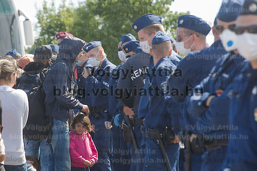 Line of police officers stands guard at a collection point of illegal migrants with families and children among them after some of the migrants tried to break out of police custody near Roszke (about 174 km South of capital city Budapest), Hungary on September 07, 2015. ATTILA VOLGYI