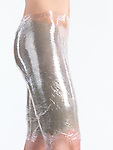 Woman with bentonite clay mask and plastic body wrap on her thighs and buttocks