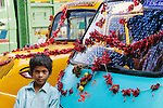 Boy stands in front of decorated taxis, Kolkata, India