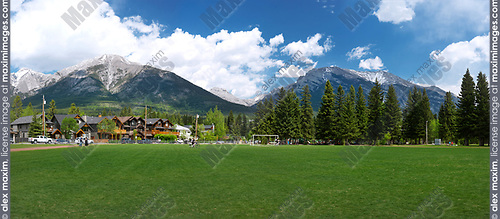 Panoramic summer scenery of Centennial Park and residetial houses in Canmore, town in Bow valley of Alberta's Rockies with Rocky mountains and beautiful nature in the background. Canmore, Alberta, Canada. 2017