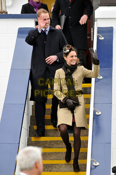 PRINCE WILLIAM & KATE MIDDLETON.Launch the new Hereford Endeavour lifeboat, Trearddur Bay Lifeboat Station, Holyhead, Isle of Anglesey.Launch of the new Hereford Endeavour lifeboat, Trearddur Bay Lifeboat Station at Anglesey,Trearddur, Wales..February 24th, 2011.couple engaged royal royals royalty full length beige coat scarf black gloves  stairs steps walking clutch bag hand waving .CAP/CAS.©Bob Cass/Capital Pictures.