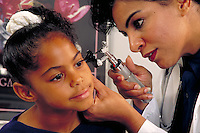 Hispanic pediatrician examines girl