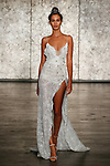 Model walks runway in a spaghettie strap jeweled lace slip dress with side drape, from Inbal Dror Fall 2018 bridal collection on October 5, 2017; during New York Bridal Fashion Week.