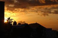 Sunrise behind palm mountain and silhouetted building. San Miguel, Santa Cruz de Tenerife. Canary Islands , Spain.